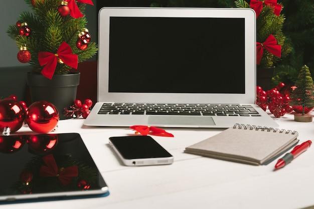 Bloc-notes ouvert et ordinateur sur table avec décor de noël Photo Premium