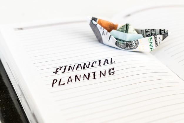 Bloc-notes ouvert avec le texte manuscrit planification financière Photo Premium