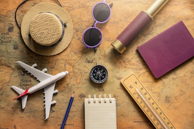 Bloc-notes pour note avec passeport, jumelles, crayon, boussole, avion sur carte papier pour image de voyage aventure découverte Photo Premium