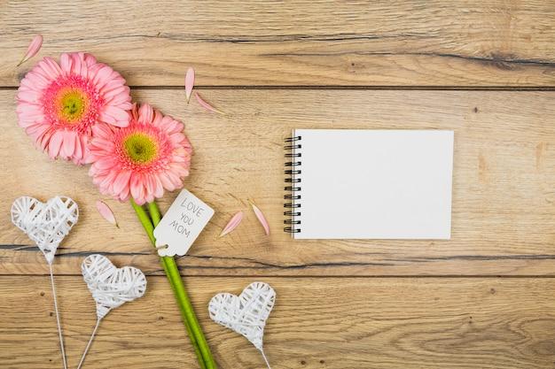 Bloc-notes Près De Fleurs Fraîches Avec étiquette Près De Coeurs D'ornement Photo gratuit