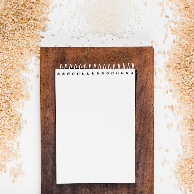 Bloc-notes spirale blanc sur planche à découper avec du riz brun et blanc sur fond blanc Photo gratuit