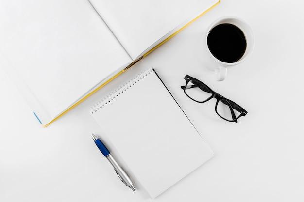 Bloc-notes en spirale; lunettes; tasse; stylo et livre sur fond blanc Photo gratuit
