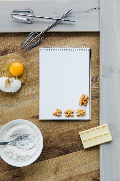 Bloc-notes en spirale; noyer; chocolat; farine; oeuf et fouet sur une surface en bois Photo gratuit