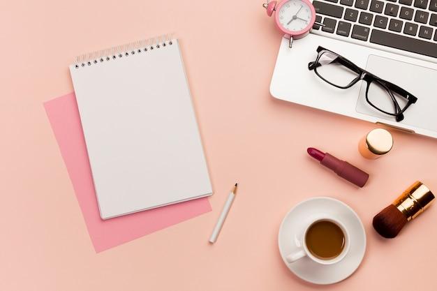 Bloc-notes à spirale avec ordinateur portable, lunettes, ordinateur portable, produit de maquillage et tasse à café sur fond coloré Photo gratuit