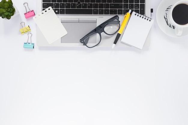Bloc-notes en spirale; stylo; lunettes, ordinateur portable, à, tasse café, et, trombones, sur, bureau blanc Photo gratuit