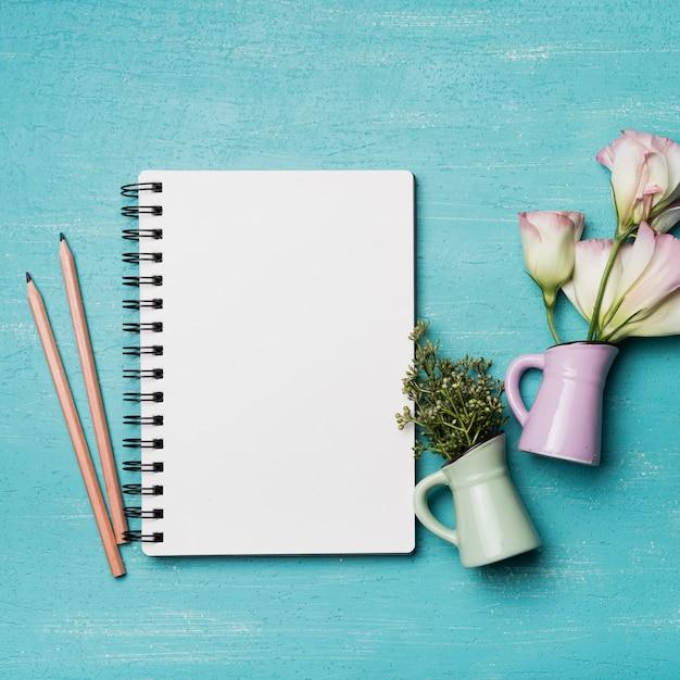 Bloc-notes spirale vierge avec deux crayons et vases sur fond bleu texturé Photo gratuit