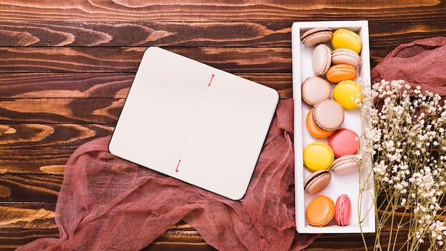 Bloc-notes en spirale vierge; macaron blanc boîte en bois et gypsophila sur toile de lin Photo gratuit