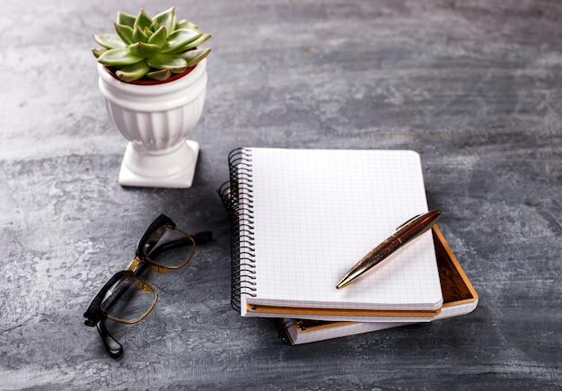 Bloc-notes avec stylo, lunettes, fleur business concept Photo Premium