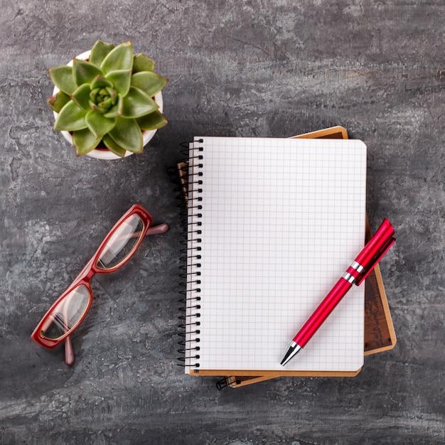 Bloc-notes avec stylo, lunettes et fleur. concept d'affaires Photo Premium