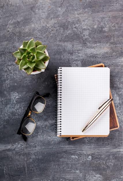Bloc-notes avec stylo, lunettes et fleur Photo Premium