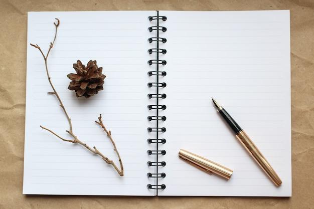 Bloc-notes, stylo en or et concert sur le bureau, table à cônes secs et branches décorées Photo Premium