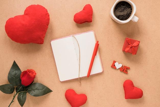 Bloc-notes avec stylo près de coeurs d'ornement, de fleurs et d'une tasse de boisson Photo gratuit