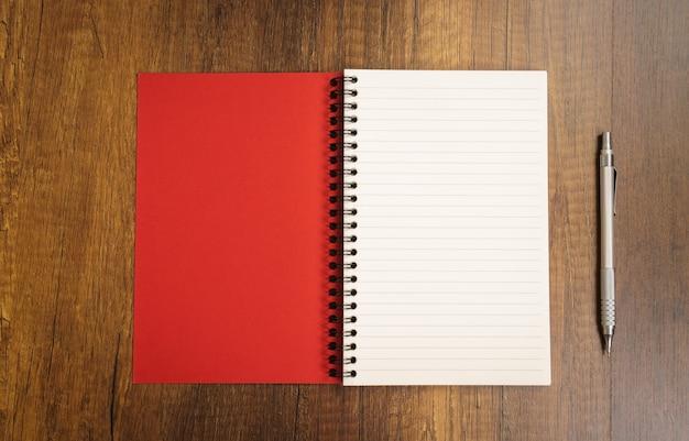 Bloc-notes avec un stylo rouge à proximité Photo gratuit