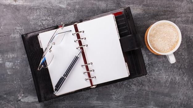 Bloc-notes avec stylo, verres, café business concept Photo Premium