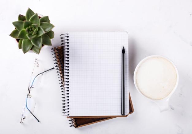 Bloc-notes avec stylo, verres, café, fleur business concept Photo Premium