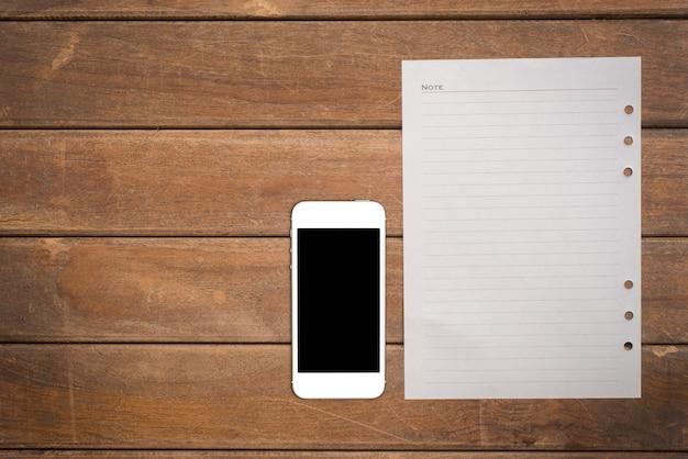 Bloc-notes avec téléphone intelligent sur la table en bois de bureau. Photo gratuit