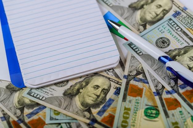Bloc-notes vide sur les billets en dollars avec un stylo Photo Premium