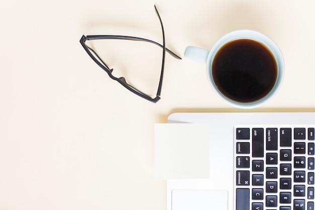 Bloc-notes vide sur ordinateur portable avec lunettes et tasse à thé sur fond beige Photo gratuit