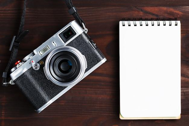 Bloc-notes vierge et appareil photo moderne de style classique sur une table en bois marron foncé Photo Premium