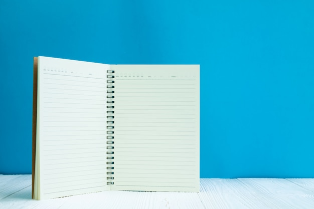 Bloc-notes vierge sur fond de mur bleu devant une table en bois blanc avec espace de copie pour ajouter du texte ou un mot publicitaire. Photo Premium