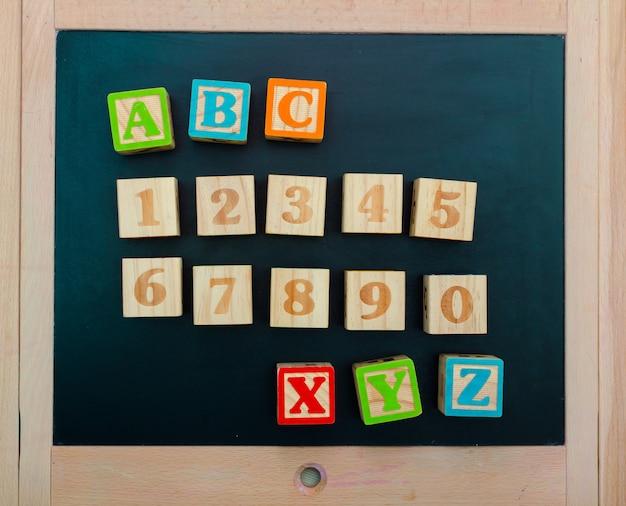 Blocs d'alphabet en bois avec des lettres et des chiffres sur une planche en bois Photo Premium