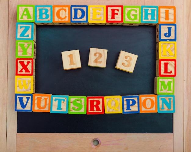 Blocs d'alphabet en bois avec des lettres sur une planche de bois Photo Premium