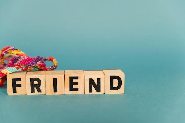 Blocs de bois avec des amis du texte et des bracelets multicolores Photo gratuit