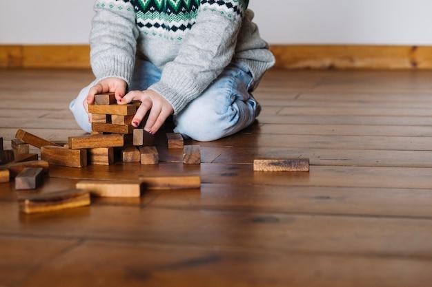 Blocs de bois de construction de main de la jeune fille Photo gratuit