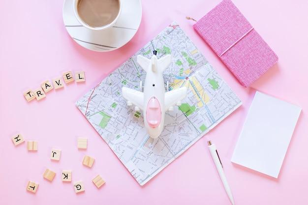 Blocs de bois de voyage; carte; papier; tasse de thé; stylo; journal et avion sur une surface blanche Photo gratuit