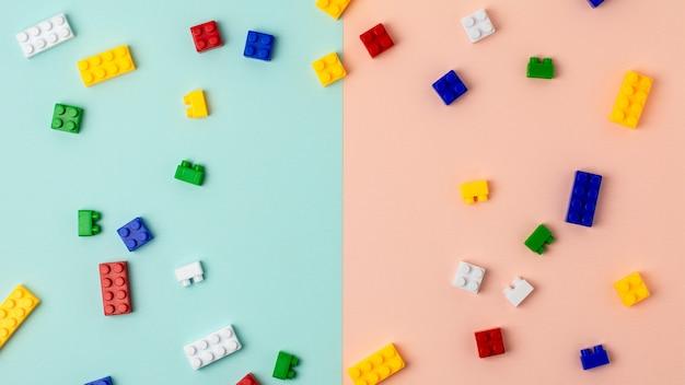 Blocs de construction en plastique sur fond bleu et rose Photo Premium