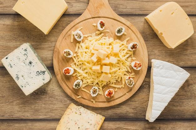 Blocs de fromage entourés près de la planche à découper en bois sur un bureau en bois Photo gratuit