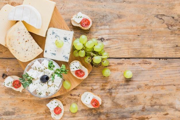 Blocs de fromage et raisins avec du pain sur une table en bois Photo gratuit