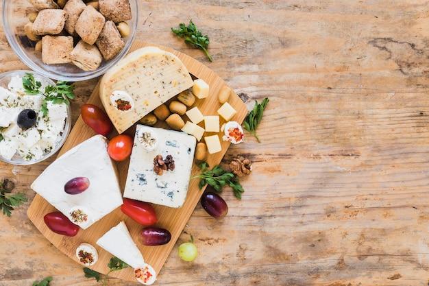 Blocs de fromage avec des tomates, du persil et des raisins sur une table en bois Photo gratuit
