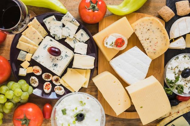 Blocs de fromage et des tranches avec des tomates, des raisins et du piment vert sur la table Photo gratuit