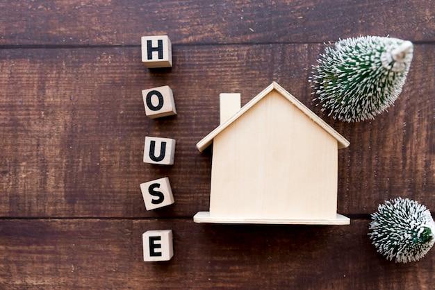 Blocs de lettre maison près du modèle de la succession avec deux sapins de noël sur fond texturé en bois Photo gratuit