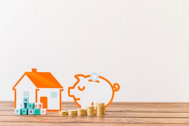 Blocs mathématiques, augmentant les pièces empilées devant la maison et tirelire sur le plancher en bois Photo gratuit