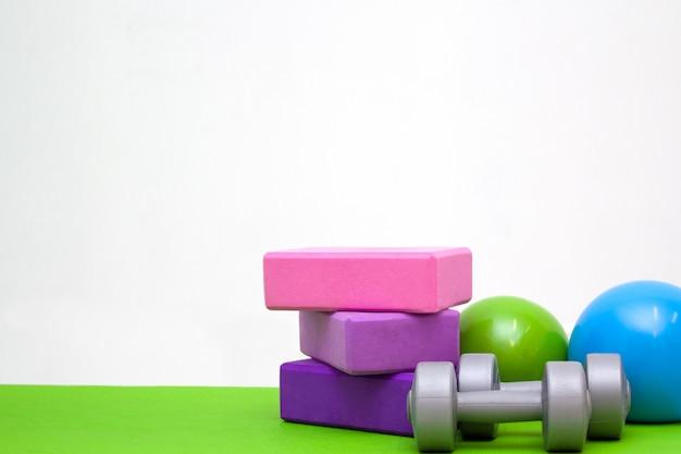 Blocs roses et violets, balles et haltères sur tapis vert. Photo Premium
