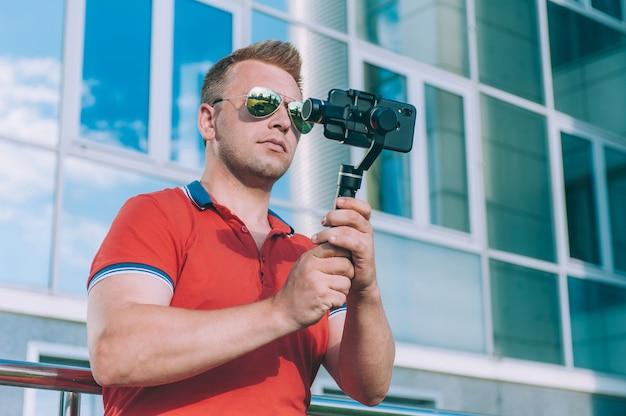 Blogger Dans La Ville Enregistre Des Vidéos Sur Un Smartphone Avec Un Stabilisateur Manuel De L'appareil Photo. Photo Premium