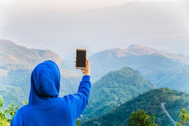 Blogueur hipster utilisant un téléphone intelligent prenant des photos au sommet de la montagne de doi angkhang, chiangmai, thaïlande. Photo Premium
