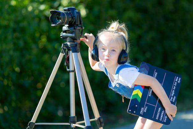 Blogueur vidéo enfant novice avec une caméra et un trépied. Photo Premium