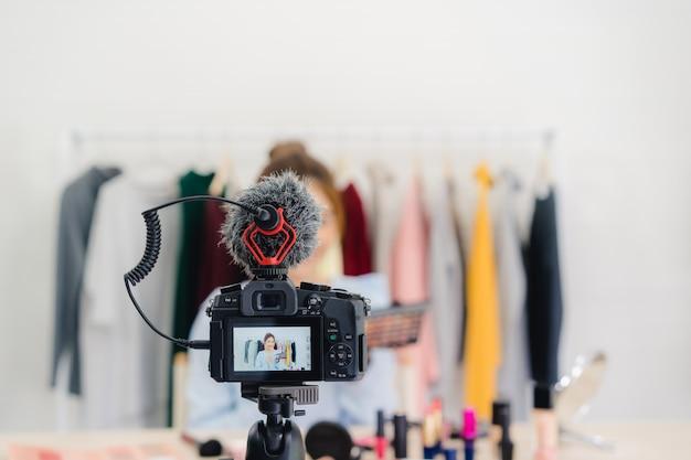 Une blogueuse beauté présente des produits de beauté assis devant la caméra pour enregistrer une vidéo Photo gratuit