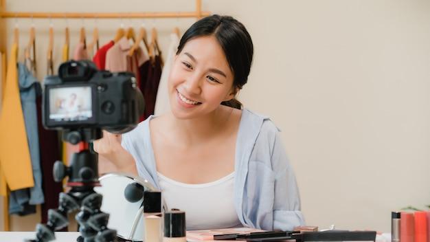 Une blogueuse beauté présente des produits cosmétiques assis devant la caméra pour enregistrer une vidéo. Photo gratuit