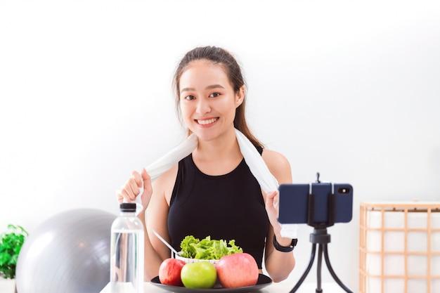 Blogueuse En Bonne Santé Femme Asiatique Montre Pomme Fruite Et Nourriture De Régime Propre. Photo Premium