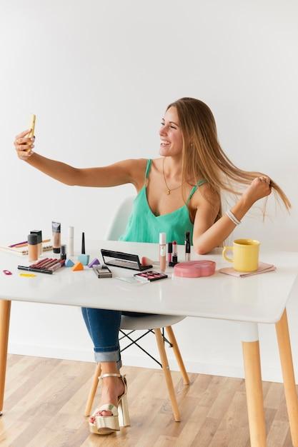Une blogueuse vue de face prenant des selfies Photo gratuit