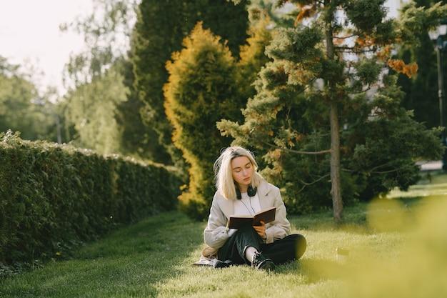 Blonde Assise Sur L'herbe Avec Un Casque Photo gratuit