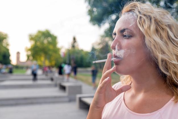 Blonde dégustant une cigarette Photo Premium