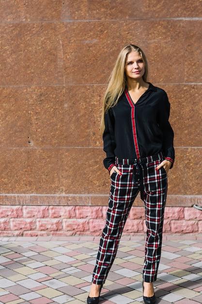 Blonde élégante jeune femme debout devant le mur Photo gratuit