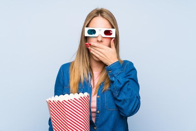 Blonde femme mangeant des popcorns couvrant la bouche avec les mains Photo Premium