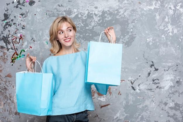 Blonde femme regardant des sacs en papier Photo gratuit