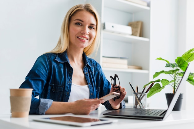 Blonde femme travaillant sur smartphone et lunettes Photo gratuit